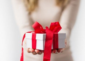 Woman holding white present box with red ribbon